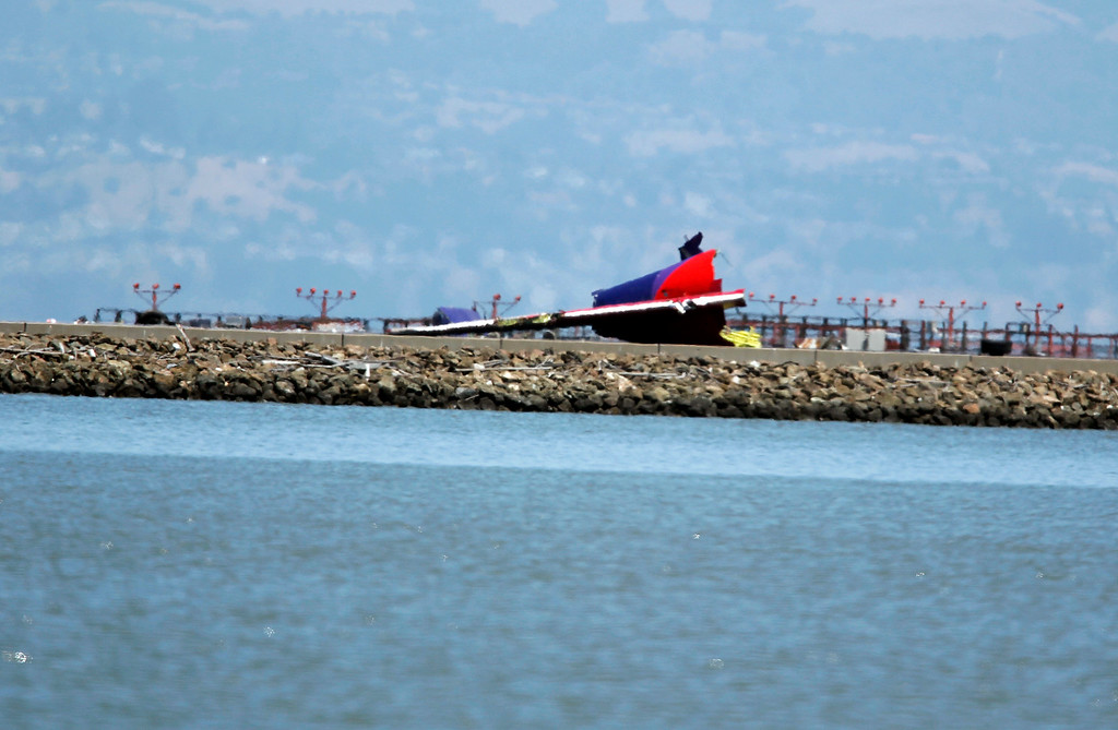 . The tail of Asiana Airlines Flight 214, a Boeing 777 arriving from Seoul, South Korea, is seen after the plane crashed on runway 28L at San Francisco International Airport, San Francisco, Calif. on Saturday July 6, 2013.  (LiPo Ching /Bay Area News Group)