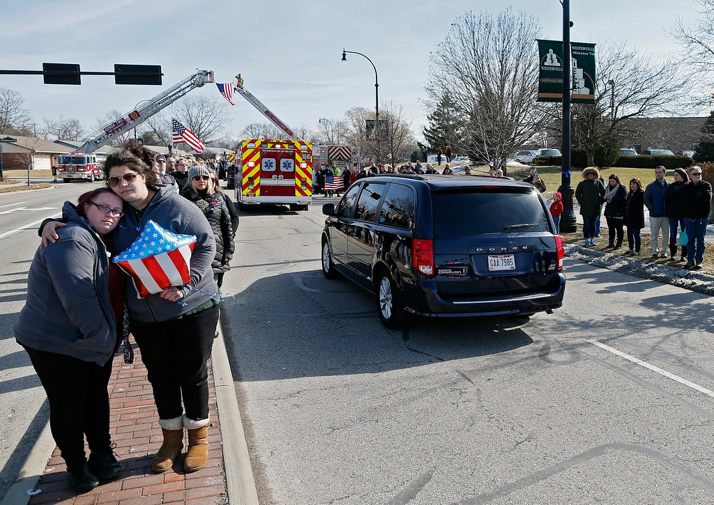 . Lindsay Evans, right, holds friend Rachel Kaczmarek, left, as the the bodies of Westerville Police officers Morelli and Joering pass by from Franklin County Coroners Monday, Feb. 12, 2018. Evans and Kaczmarek has officer Morelli as a resource officer in middle school. (Kyle Robertson/The Columbus Dispatch via AP)