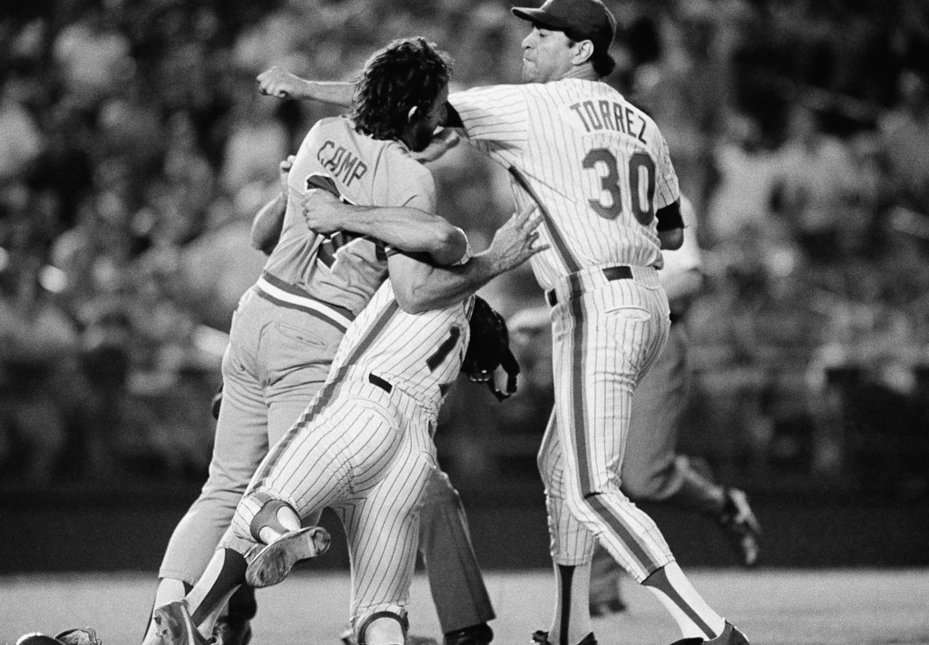 . New York pitcher Mike Torrez takes a swing at Atlanta Braves\' pitcher Rick Camp as first baseman Keith Hernandez attempts to intercede in the sixth inning of game at New York\'s Shea Stadium,  July 26, 1983. Torrez had hit Camp with a pitch and the Atlanta pitcher then charged the mound. Earlier ,Camp had hit the Mets Mookie Wilson with a pitch. No one was thrown cut of the game. (AP Photo/Ray Stubblebine)
