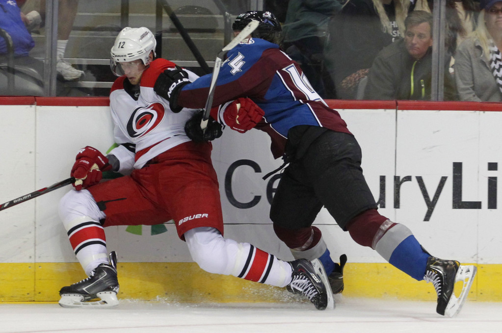 . Colorado Avalanche defenseman Ryan Wilson (44) checks Carolina Hurricanes center Eric Staal (12) in the second period of an NHL hockey game in Denver on Friday, Oct. 25, 2013.(AP Photo/Joe Mahoney)