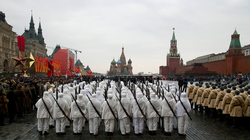 . Russian soldiers wear snow gear over Red Army World War II uniforms as they prepare to parade in Red Square in front of St. Basil Cathedral, center, and Spassky Tower, right,  in Moscow, Russia, Thursday, Nov. 7, 2013. Thousands of Russian soldiers and military cadets marched across Red Square to mark the 72nd anniversary of a historic World War II parade. The show honored the participants of the Nov. 7, 1941 parade who headed directly to the front lines to defend Moscow from the Nazi forces. The parade Thursday involved about 6,000 people, many of them dressed in World War II-era uniforms. (AP Photo/Alexander Zemlianichenko)