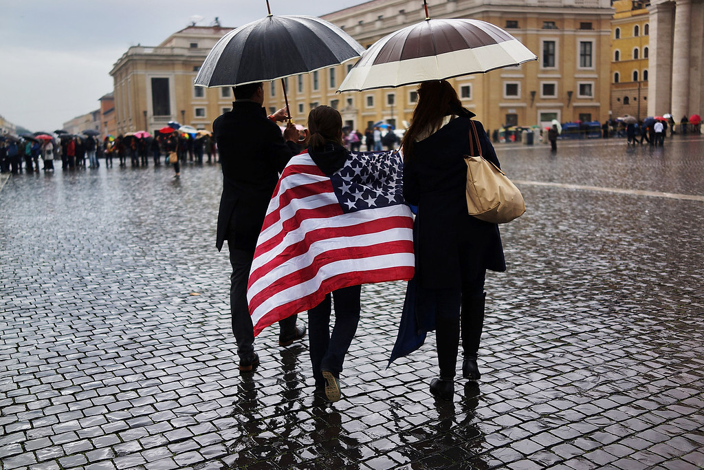 . A woman walks across St Peter\'s Square in an American flag as others wait for smoke to emanate from the chimney on the roof of the Sistine Chapel which will indicate whether or not the College of Cardinals have elected a new Pope on March 13, 2013 in Vatican City, Vatican. (Photo by Spencer Platt/Getty Images)