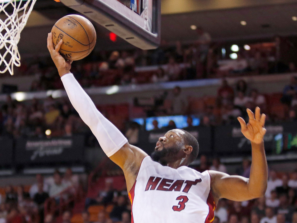 . CORRECTS DAY OF WEEK - Miami Heat guard Dwyane Wade (3) leaps to score against the Detroit Pistons in the first half of an NBA basketball game, Sunday, March 29, 2015, in Miami. (AP Photo/Joe Skipper)