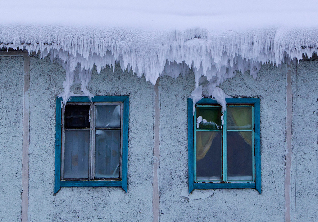 . The roof of a house is covered with snow in the village of Tomtor in the Oymyakon valley in the Republic of Sakha, northeast Russia, January 24, 2013. The coldest temperatures in the northern hemisphere have been recorded in Sakha, the location of the Oymyakon valley, where according to the United Kingdom Met Office a temperature of -67.8 degrees Celsius (-90 degrees Fahrenheit) was registered in 1933 - the coldest on record in the northern hemisphere since the beginning of the 20th century. Yet despite the harsh climate, people live in the valley, and the area is equipped with schools, a post office, a bank, and even an airport runway (albeit open only in the summer). Picture taken January 24, 2013.  REUTERS/Maxim Shemetov