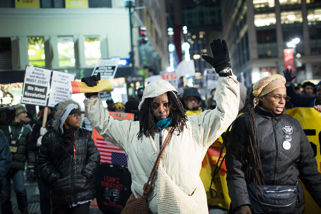 . NEW YORK, NY - DECEMBER 31:  An activist holds her hands up during a protest march against police brutality that traveled from Union Square to Times Square on December 31, 2014 in New York City. The protest group was turned away from Times Square at 38th Street. Governor Andrew Cuomo today announced the New York Army and Air National Guard will have an increased presence during this New Year\'s Eve, conducting extra security missions throughout New York City.  (Photo by Kevin Hagen/Getty Images)