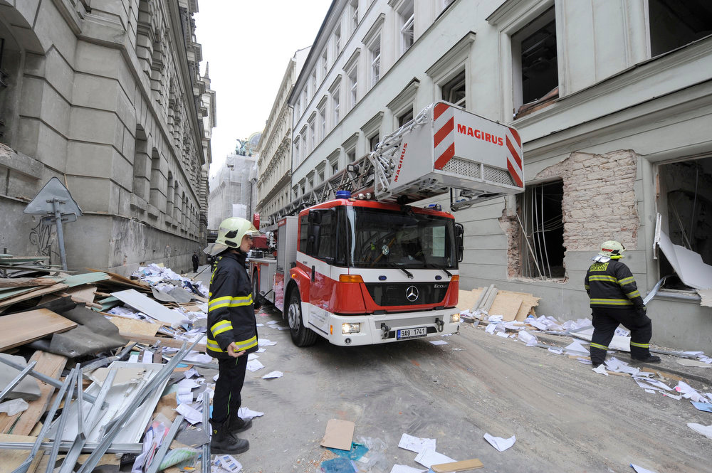 . A fire engine arrives at the scene of a strong blast in a building in the centre of Prague, Czech Republic, Monday, April 29, 2013. After the explosion, probably caused by gas leak, there are some 40 injuries, mostly light. The blast broke windows in a broad vicinity, a number of people have been cut by the glass. Rescuers are still looking for possible people under the debris. (AP Photo/CTK, Stanislav Zbynek)