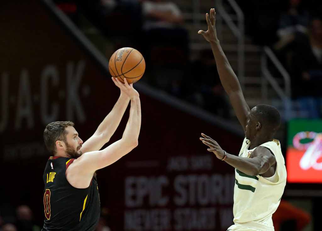 . Cleveland Cavaliers\' Kevin Love, left, shoots over Milwaukee Bucks\' Thon Maker, from Australia, in the second half of an NBA basketball game, Monday, March 19, 2018, in Cleveland. (AP Photo/Tony Dejak)