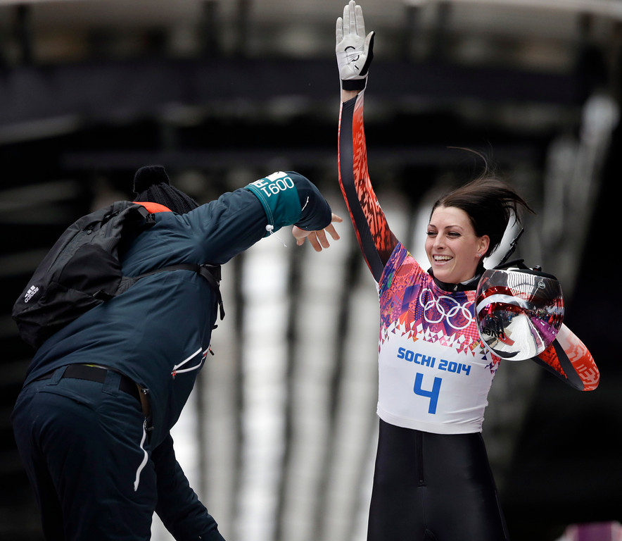 . Janine Flock of Austria high-fives her coach after her final run during the women\'s skeleton competition at the 2014 Winter Olympics, Friday, Feb. 14, 2014, in Krasnaya Polyana, Russia. (AP Photo/Dita Alangkara)