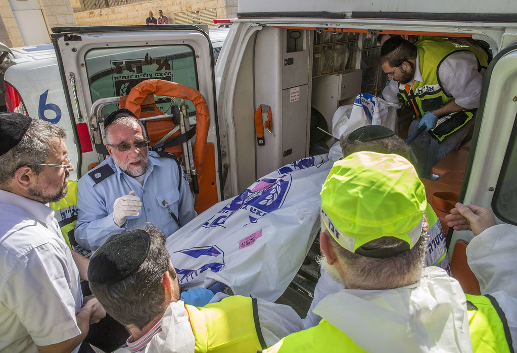 . Israeli Zaka emergency services volunteers load the body of one of the two Palestinian assailants who were shot dead while attacking worshippers at a synagogue into an ambulance in the ultra-Orthodox Har Nof neighborhood in Jerusalem on November 18, 2014. Two Palestinians armed with a gun and axes burst into a Jerusalem synagogue and killed four Israelis before being shot dead, in the deadliest attack in the city in years.  AFP PHOTO / JACK GUEZ/AFP/Getty Images