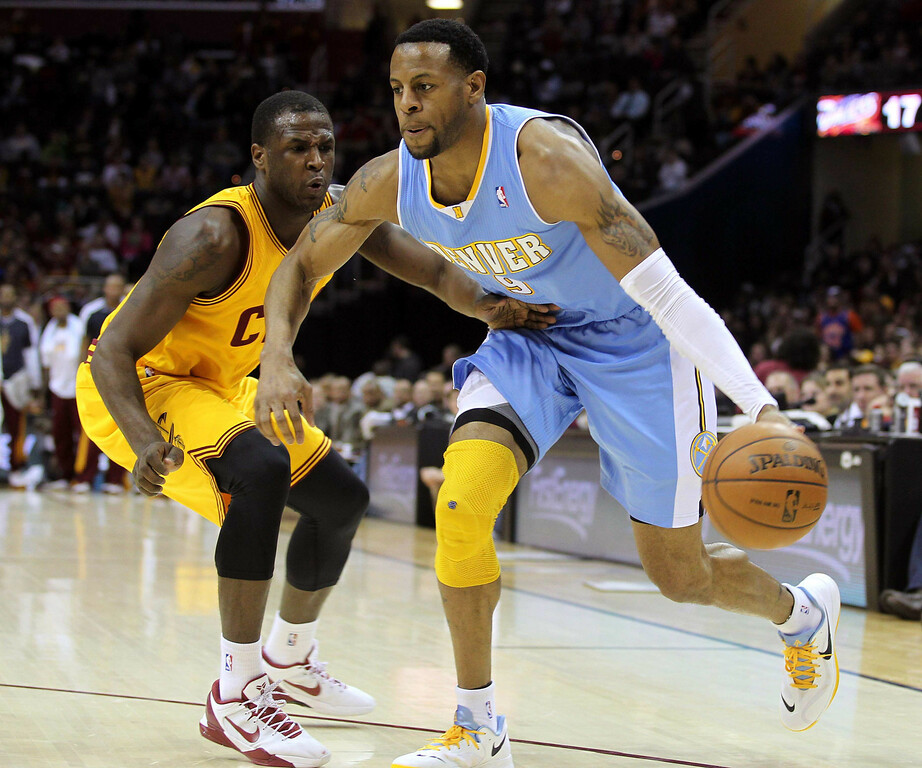 . Denver Nuggets Andre Iguodala (R) drives to the basket past the defense of Cleveland Cavaliers Dion Waiters (L) during the first quarter of their NBA basketball game in Cleveland, February 9, 2013.   REUTERS/Aaron Josefczyk