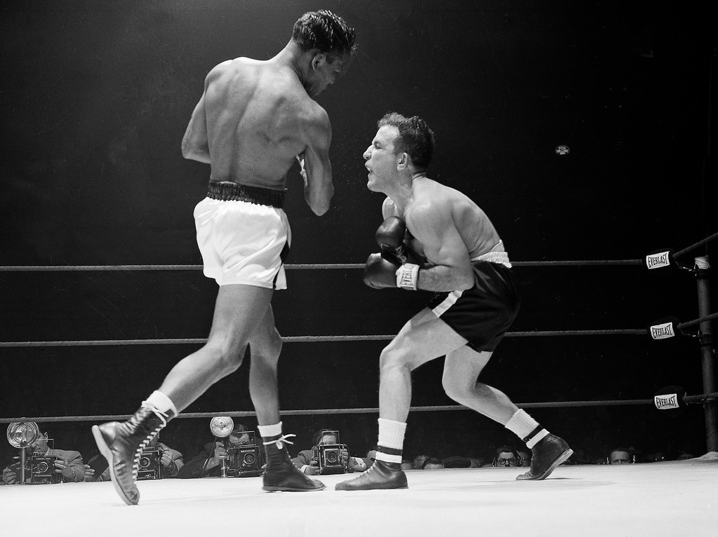 . Jake LaMotta, right, bends over and yelps after taking a stinging right from defending champion Sugar Ray Robinson in the third round of their Middleweight Championship fight at Chicago Stadium, Chicago, Feb. 14, 1951. (AP Photo)
