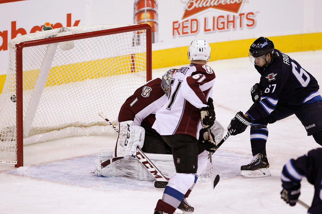 . Winnipeg Jets\' Michael Frolik (67) deflects Jacob Trouba\'s (8) shot for the goal against Colorado Avalanche\'s goaltender Semyon Varlamov (1) and Andre Benoit (61) during first period NHL hockey action in Winnipeg, Manitoba,  on Thursday, Dec. 12, 2013. (AP Photo/The Canadian Press, John Woods)