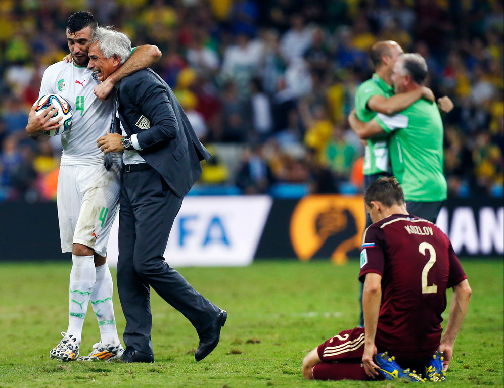 . Algeria\'s Essaid Belkalem and head coach Vahid Halilhodzic embrace as Russia\'s Alexei Kozlov, right, reacts after the group H World Cup soccer match between Algeria and Russia at the Arena da Baixada in Curitiba, Brazil, Thursday, June 26, 2014. With Algeria and Russia playing to a 1-1 draw, Algeria qualified for the knock-out stage. (AP Photo/Jon Super)