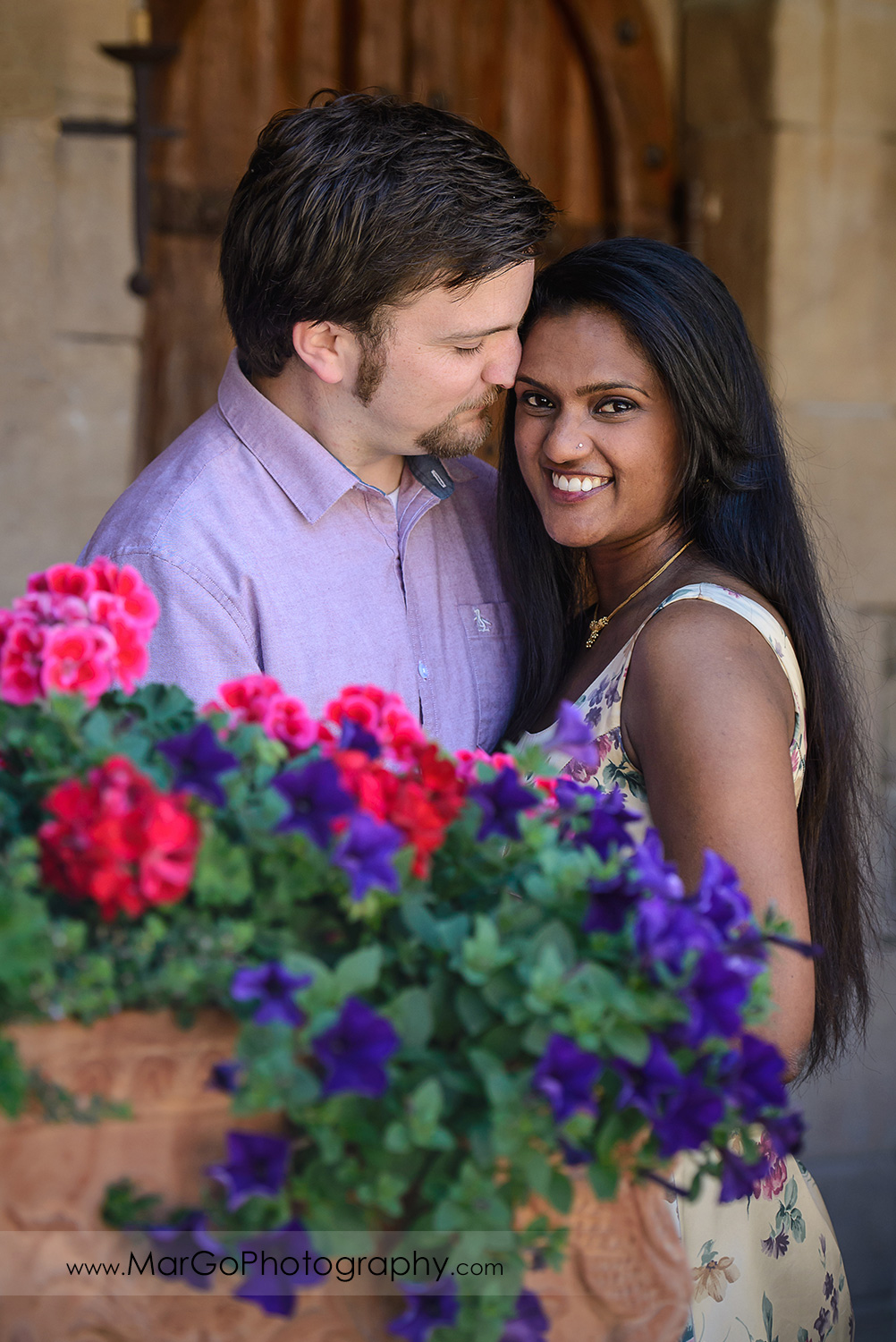 portrait of man in pink shirt looking at Indian woman in flower dress looking into camera during engagement session at Castello di Amorosa in Calistoga