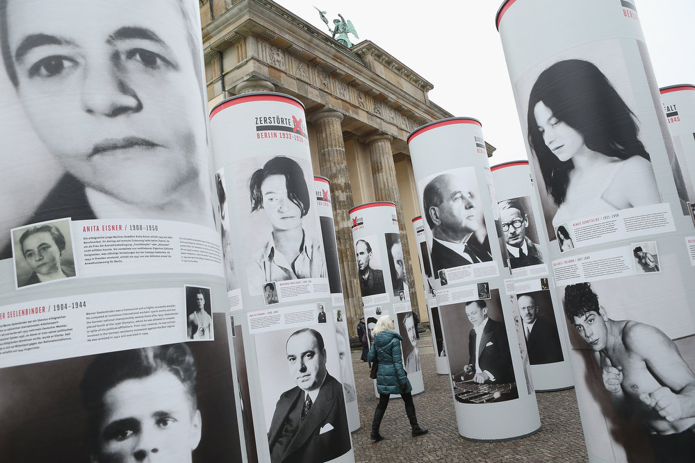 Description of . A visitor walks among portraits of Berlin Jews and political opponents persecuted, and in many cases murdered or driven to suicide, by the Nazis in the exhibition