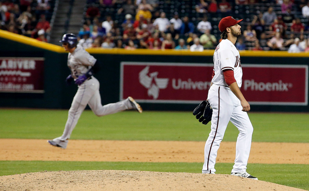 . Arizona Diamondbacks\' Mike Bolsinger, right, looks away as Colorado Rockies\' Troy Tulowitzki (2) rounds the bases after hitting a two-run home run during the sixth inning of a baseball game on Tuesday, April 29, 2014, in Phoenix. (AP Photo/Ross D. Franklin)