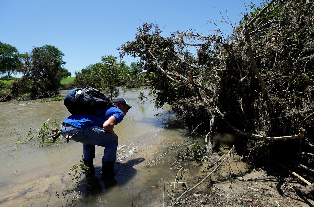. Search and rescue volunteer Chad Hartsman searches a flood damaged area Friday May, 29, 2015, in San Marcos, Texas. Search efforts continue for those persons who went missing  from the Memorial Day weekend floods in Central Texas. (AP Photo/Eric Gay)