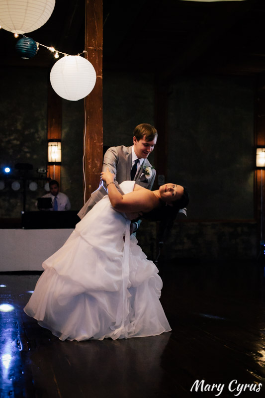 Matt dips his bride, Larissa, during their first dance at the McKinney Cotton Mill | Photo by Mary Cyrus Photography - Weddings & Portraits in Dallas & Beyond