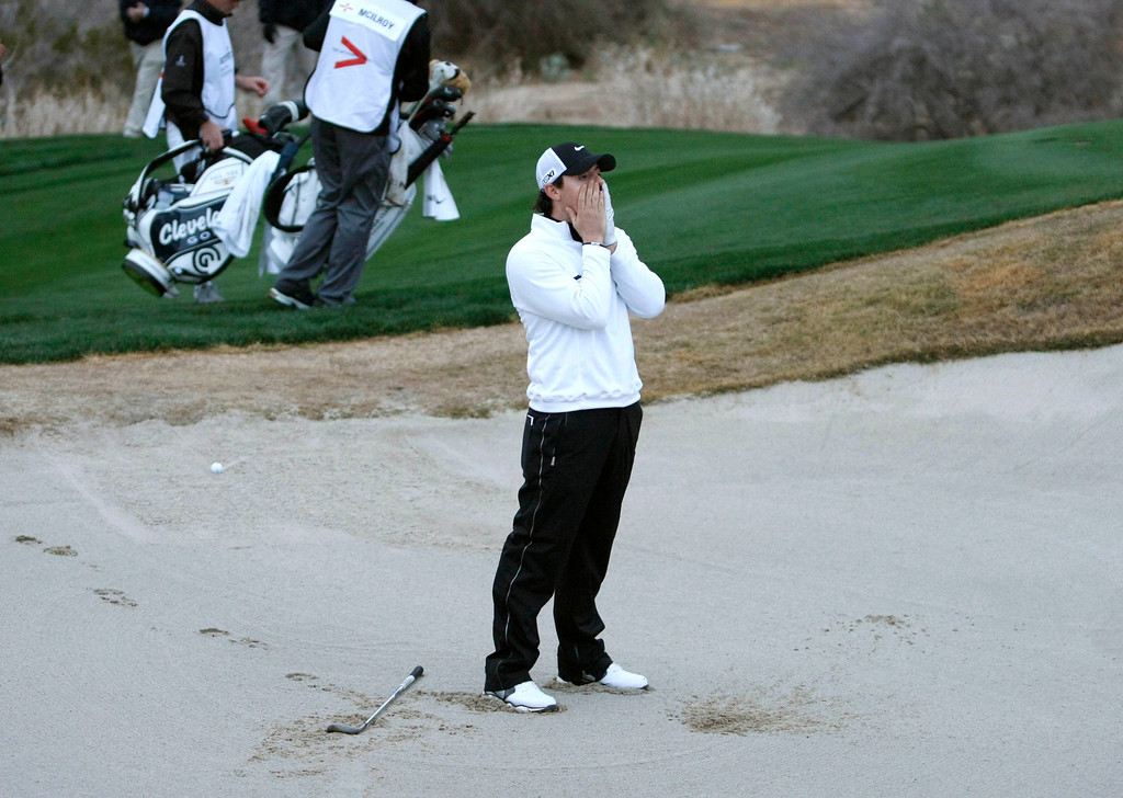 . Northern Ireland\'s Rory McIlroy reacts after hitting out of the sand on the 18th in loss to Shane Lowry of Ireland  during the weather delayed first round of the WGC-Accenture Match Play Championship golf tournament in Marana, Arizona February 21, 2013. REUTERS/Ralph Freso