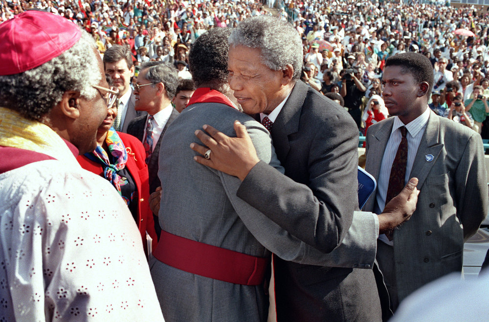 Description of . African National Congress (ANC) and president-to-be Nelson Mandela (C), flanked by bodyguards, hugs Archbishop Manas Buthelezi as Anglican archbishop Desmond Tutu (L) looks on, 08 May 1994, during a national thanks giving prayer service near Soweto. Mandela urged South Africans of all races to forget the past and join hands in building a united country. (Photo credit should read WALTER DHLADHLA/AFP/Getty Images)