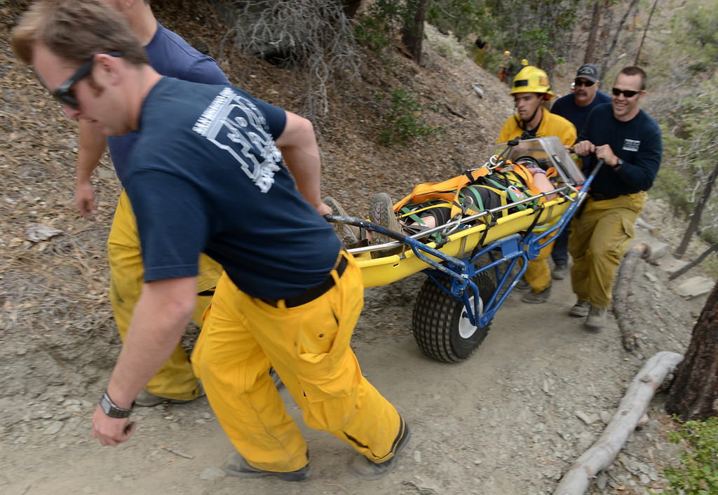 . San Bernardino and Los Angeles county firefighters pull a subject out of a canyon during a training with zip line and helicopter hoist rescues in Wrightwood May 13, 2013. The training will help when hikers get lost or injured and need to be rescued.  (Thomas R. Cordova/Staff Photographer)