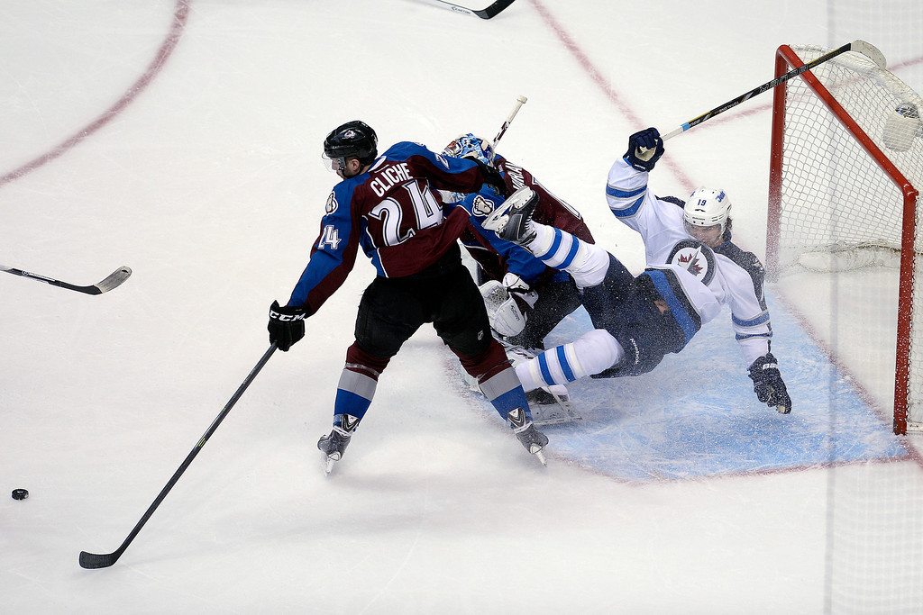 . Jim Slater (19) of the Winnipeg Jets falls over Semyon Varlamov (1) of the Colorado Avalanche as Marc-Andre Cliche (24) helps to defend the crease during the first period. (Photo by AAron Ontiveroz/The Denver Post)