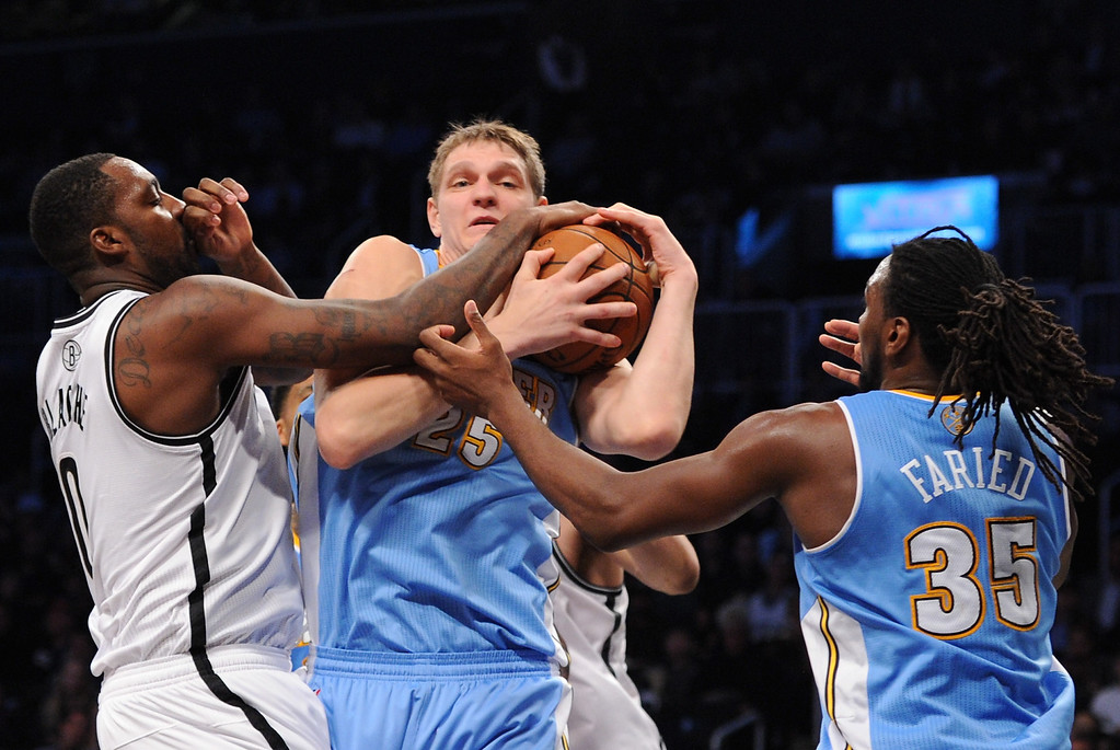 . NEW YORK, NY - DECEMBER 03:  Timofey Mozgov #25 and Kenneth Faried #35 of the Denver Nuggets battle with Andray Blatche #0 of the Brooklyn Nets for a rebound during the first half at Barclays Center on December 3, 2013 in the Brooklyn borough of New York City. The Nuggets defeat the Nets 111-87. (Photo by Maddie Meyer/Getty Images)
