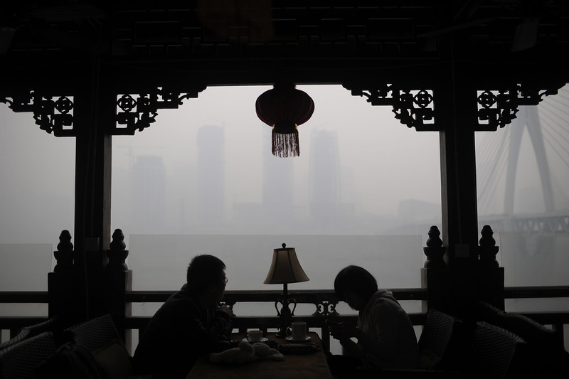 . People chat in a teahouse on the river bank in the haze in southwest China\'s Chongqing Municipality 23 February 2014. The weather authority said haze covered 1.43 million square meters in China 22 February, more than one seventh of China\'s territory.  (EPA/RAN WEN)