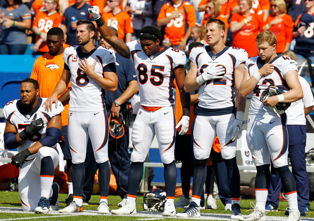 . Denver Broncos tight end Virgil Green (85) gestures and offensive guard Max Garcia, left, kneels during the playing of the national anthem prior to an NFL football game against the Buffalo Bills, Sunday, Sept. 24, 2017, in Orchard Park, N.Y. (AP Photo/Jeffrey T. Barnes)