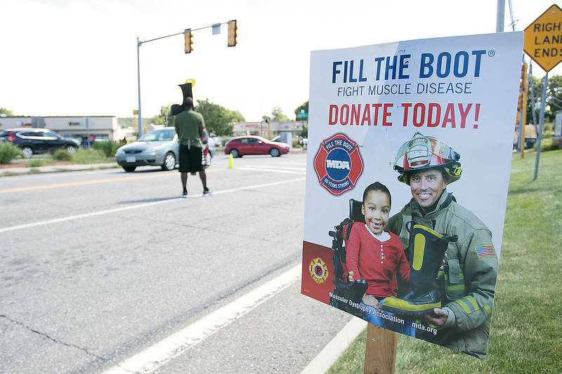 Nine year veteran of the Fitchburg Fire Deparment Yona Vaughan was on Bemis Road in the city Thursday collecting for the Muscular Dystrophy Association. He made a hat/mask that look like a boot to help cheer up people that stopped to donate. SENTINEL & ENTERPRISE/JOHN LOVE
