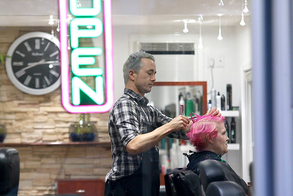 """. James Schneider the owner of HairXotica in Fitchburg puts the finishing touches on Kathy DiRusso pink hair on Tuesday night, May 30, 2017. For the 11th year DiRusso went \""""PINK\"""" for the cure. This is to help raise money and awareness for her teams Susan G Komen 3 day for the Cure for breast cancer walk. SENTINEL & ENTERPRISE/JOHN LOVE"""