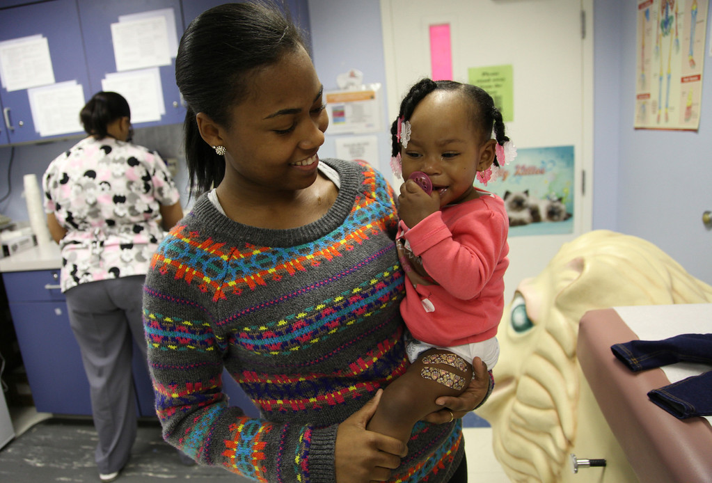. La\'Naiya Broughton, 1, from Oakland, recovers in her mother\'s arms, LaTasha Bankhead, after getting  three immunizations at the Children\'s Hospital Primary Care Clinic in Oakland, Calif.,on Wednesday, Jan. 16, 2013.  The Institute of Medicine released a report Wednesday declaring the recommended childhood immunization schedule to be safe. (Laura A. Oda/Staff)