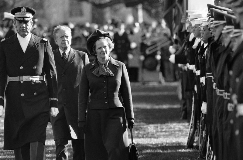 """. In this Dec. 17, 1979 file photo, British Prime Minister Margaret Thatcher  reviews the honor guard at the White House in Washington, as President Jimmy Carter follows.  At left in Col. Stanley Bonta, commander of the guard. Ex-spokesman Tim Bell says that Thatcher has died. She was 87. Bell said the woman known to friends and foes as \""""the Iron Lady\"""" passed away Monday morning, April 8, 2013. (AP Photo/File)"""