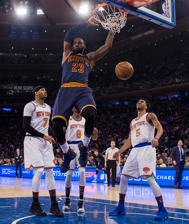 . Cleveland Cavaliers\' LeBron James (23) dunks in front of New York Knicks\' Carmelo Anthony (7), Courtney Lee (5) and Justin Holiday (8) during the first half of an NBA basketball game, Saturday, Feb. 4, 2017, in New York. (AP Photo/Andres Kudacki)