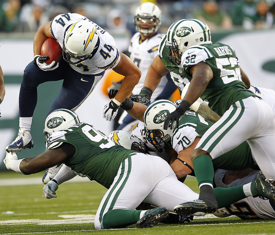 . Running back Jackie Battle #44 of the San Diego Chargers leaps over Muhammad Wilkerson #96 of the New York Jets during the second half at MetLife Stadium on December 23, 2012 in East Rutherford, New Jersey. The Chargers defeated the Jets 27-17. (Photo by Rich Schultz /Getty Images)