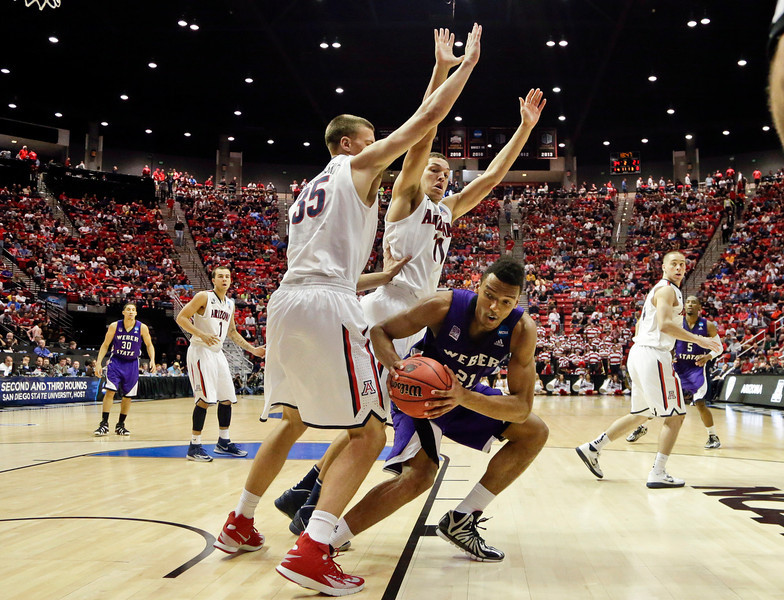 . Weber State\'s Joel Bolomboy, right, is double-teamed by Arizona\'s Kaleb Tarczewski, left, and Aaron Gordon during the second half in a second-round game in the NCAA college basketball tournament Friday, March 21, 2014, in San Diego. (AP Photo/Gregory Bull)