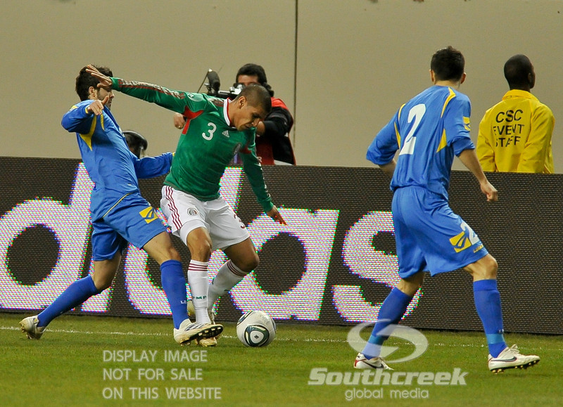 Mexico's Defender Carlos Salcido (#3) dribbles the ball away from the defender while Bosnia-Herzegovina's Defender Mensur Mujdza (#2) attempts to engage during Soccer action between Bosnia-Herzegovina and Mexico.  Mexico defeated Bosnia-Herzegovina 2-0 in the game at the Georgia Dome in Atlanta, GA.