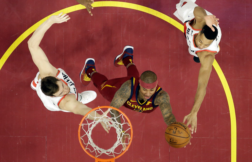 . Cleveland Cavaliers\' Isaiah Thomas, center, drives to the basket against Portland Trail Blazers\' Pat Connaughton, left, and CJ McCollum in the second half of an NBA basketball game, Tuesday, Jan. 2, 2018, in Cleveland. The Cavaliers won 127-110. (AP Photo/Tony Dejak)
