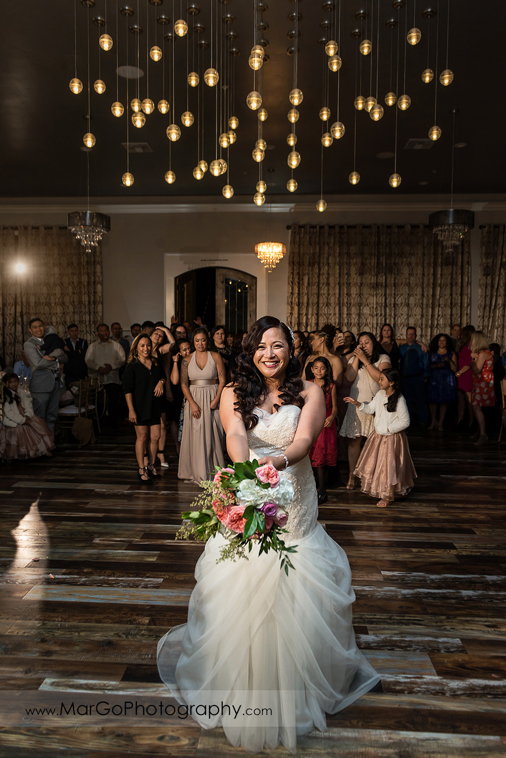 bride tossing bouquet during wedding reception at Sunol's Casa Bella