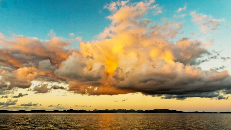 Yellow and grey colored cumulonimbus cloud, sunset seascape.
