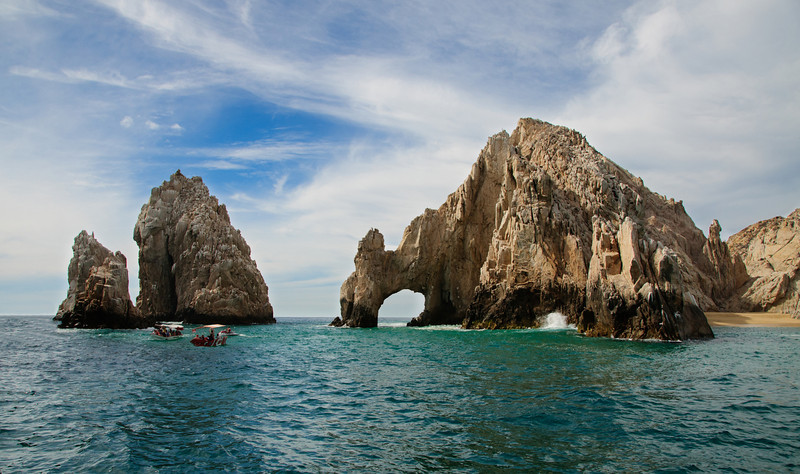 28 Feb 12.  At the very distal end of the Baja Peninsula lies Cabo San Lucas, a charming resort area on the Mexican Riviera. Although our stay there was for just a few hours, we both fell immediately in love with it and will be making many more trips there to visit and enjoy the beautiful surroundings and people. Fishing, diving, climbing, para-sailing, and photography are just a few of the treats that await any visitor. The very tip of the peninsula is comprised only of large rocks, the very furthest grouping of which is known as the Lands End, and the most famous, if you will, is the chunk of rock known as El Arco, the arch. Here the Sea of Cortez meets the Pacific Ocean, and although the water was quite calm on the day of our visit, it isn't always so. On the leeward side of the rocks (a wee bit south of where lies the city) is to be found Playa Doña Chepa, the lover's beach; only accessible by boat, it is well worth the trip. From here you can get a great view of the arch and even walk under it at low tide, at least that was my impression from viewing it three different times with differing tides. On our way down the coast I had myself positioned to get a few shots of it from a distance that would have made for some potentially nice images. As we got into position a lady simply pushed herself in front of me blocking my view and remained there for the entire opportunity. Not absolutely certain why she didn't find herself overboard and the more I've thought about it the more I think I should have made that happen! So I missed out on a nice opportunity as the water was a bit rough and the waves were breaking magnificently through the arch. On the return the water was quite calm and we saw no such action. The image you see today was taken from a tour boat that took us around both sides of El Arco as part of a sight seeing tour both above and below the water. ISO 200; 1/1000 sec @ f / 8.