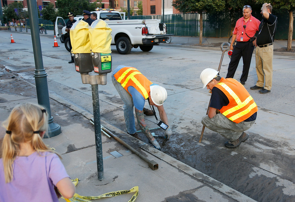 . Denver Water Department workers toil outside the main gate of Coors Field in downtown Denver after a break in a major water main forced the cancellation of a baseball game between the Cincinnati Reds and the Colorado Rockies on Saturday, Aug. 16, 2014. The game will be played on Sunday as part of a split doubleheader. (AP Photo/David Zalubowski)
