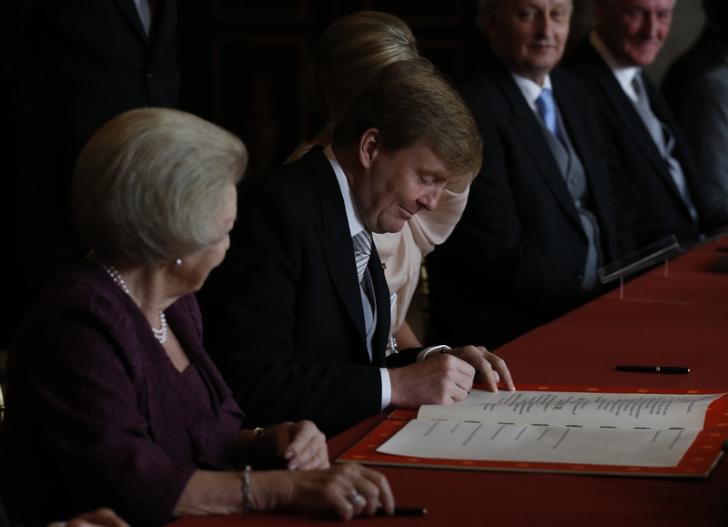 . Prince Willem-Alexander of the Netherlands signs Queen Beatrix of the Netherlands\' Act of Abdication during a ceremony held at the Royal Palace in Amsterdam on April 30, 2013.  JERRY LAMPEN/AFP/Getty Images