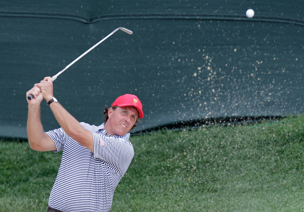 . United States\'  Phil Mickelson hits from the sand on the first hole during a foursome match against the International team at the Presidents Cup golf tournament at Muirfield Village Golf Club Friday, Oct. 4, 2013, in Dublin, Ohio. (AP Photo/Jay LaPrete)