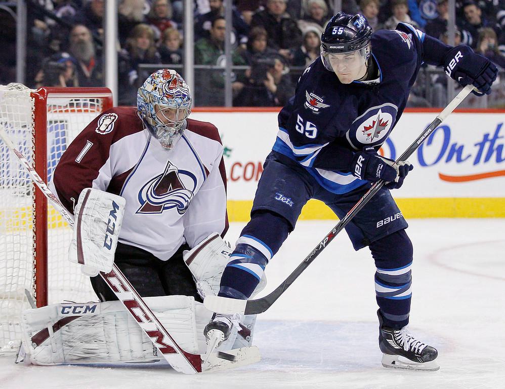 . Winnipeg Jets\' Mark Scheifele (55) attempts to deflect the shot past Colorado Avalanche\'s goaltender Semyon Varlamov (1) during second period NHL action in Winnipeg on Thursday, December 12, 2013. THE CANADIAN PRESS/John Woods