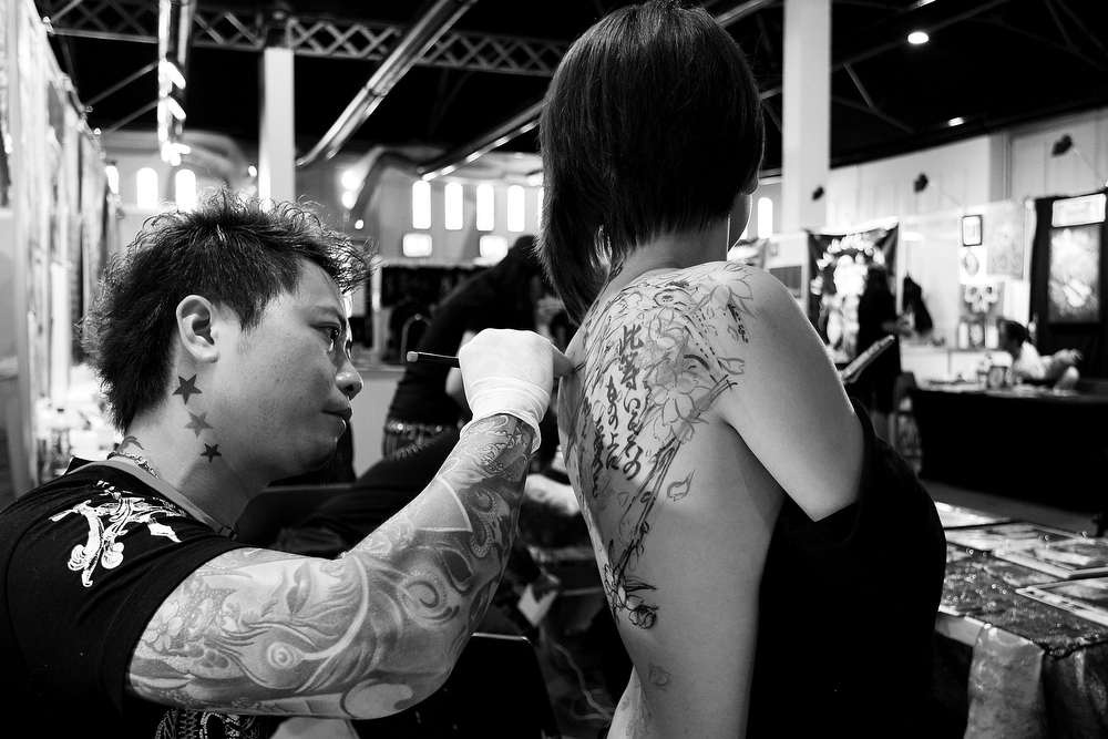 . A tattoo artist from \'Night Action Tattoo\' in Taiwan sketches on a young woman during The Australian Tattoo & Body Art Expo at the Royal Hall of Industries, Moore Park on March 8, 2013 in Sydney, Australia. The annual three day event showcases some of Australia\'s best tattoo and body artists and is open to enthusiasts March 8-10.  (Photo by Lisa Maree Williams/Getty Images)