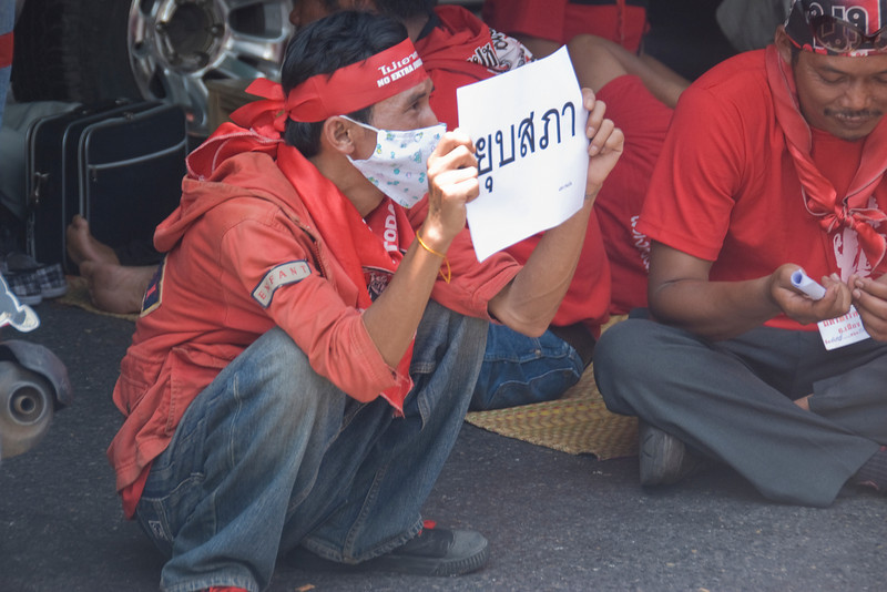 Man holding out Thai sign during Red Shirt Protest - Thailand