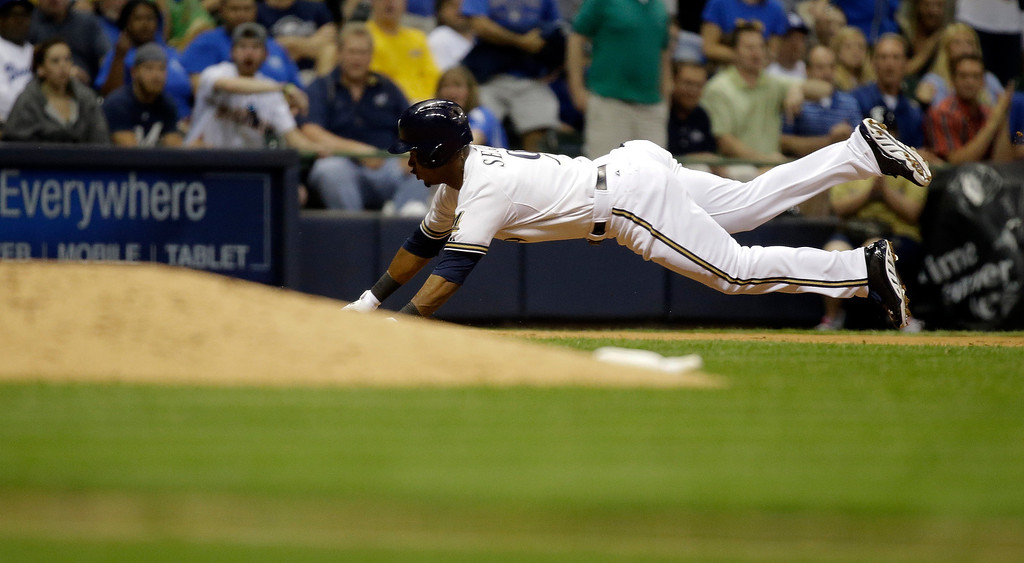 . Milwaukee Brewers\' Jean Segura slides into third for a triple during the fifth inning of a baseball game against the Los Angeles Dodgers Tuesday, May 21, 2013, in Milwaukee. (AP Photo/Morry Gash)