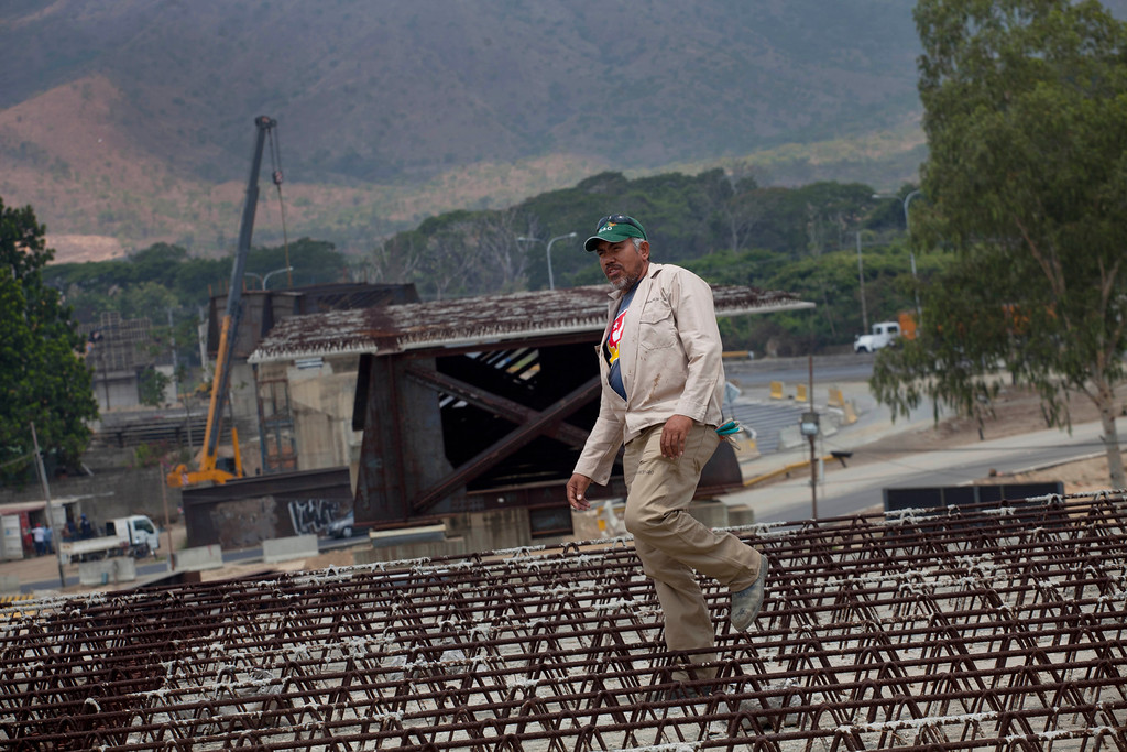 . In this April 8, 2013 photo, construction worker Anselmo Mendoza, 46, walks through rows of rebar at a bridge construction site in San Diego, Venezuela. Outside Venezuela\'s capital, power outages, food shortages and unfinished projects abound; important factors heading into Sunday\'s election to replace Venezuela\'s late President Hugo Chavez, who died last month after a long battle with cancer. Maduro, Chavez\'s hand-picked successor, has generally avoided references to public works on the campaign trail, although on a stop this week in Apure state, he did apologize for a delayed highway extension, maternity hospital and bridge. (AP Photo/Ramon Espinosa)