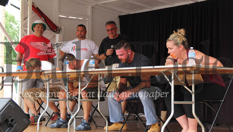 Festival-goers race to eat piles of pasta at the Butler Italian Festival. The winner of Saturday's pasta eating competition won $100. Competitors were not allowed to use their hands.  2018  Lauryn Halahurich/Butler Eagle